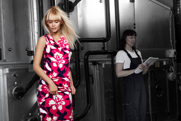 A woman with colourful dress, in the background black and white factory picture.