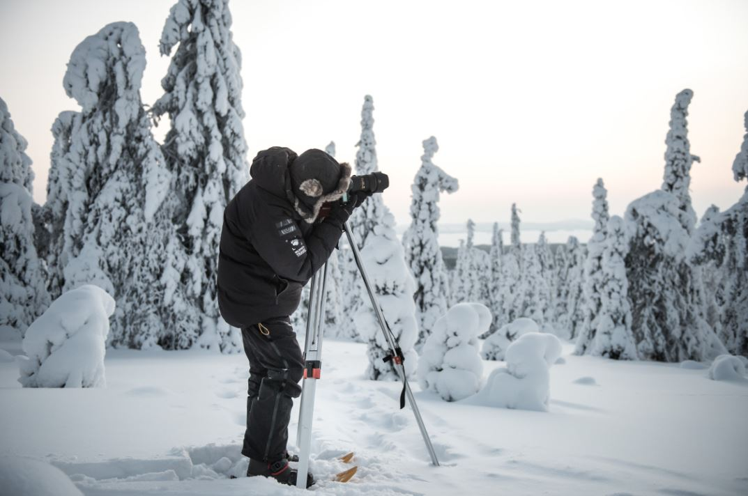 A photographer in snowy forest.