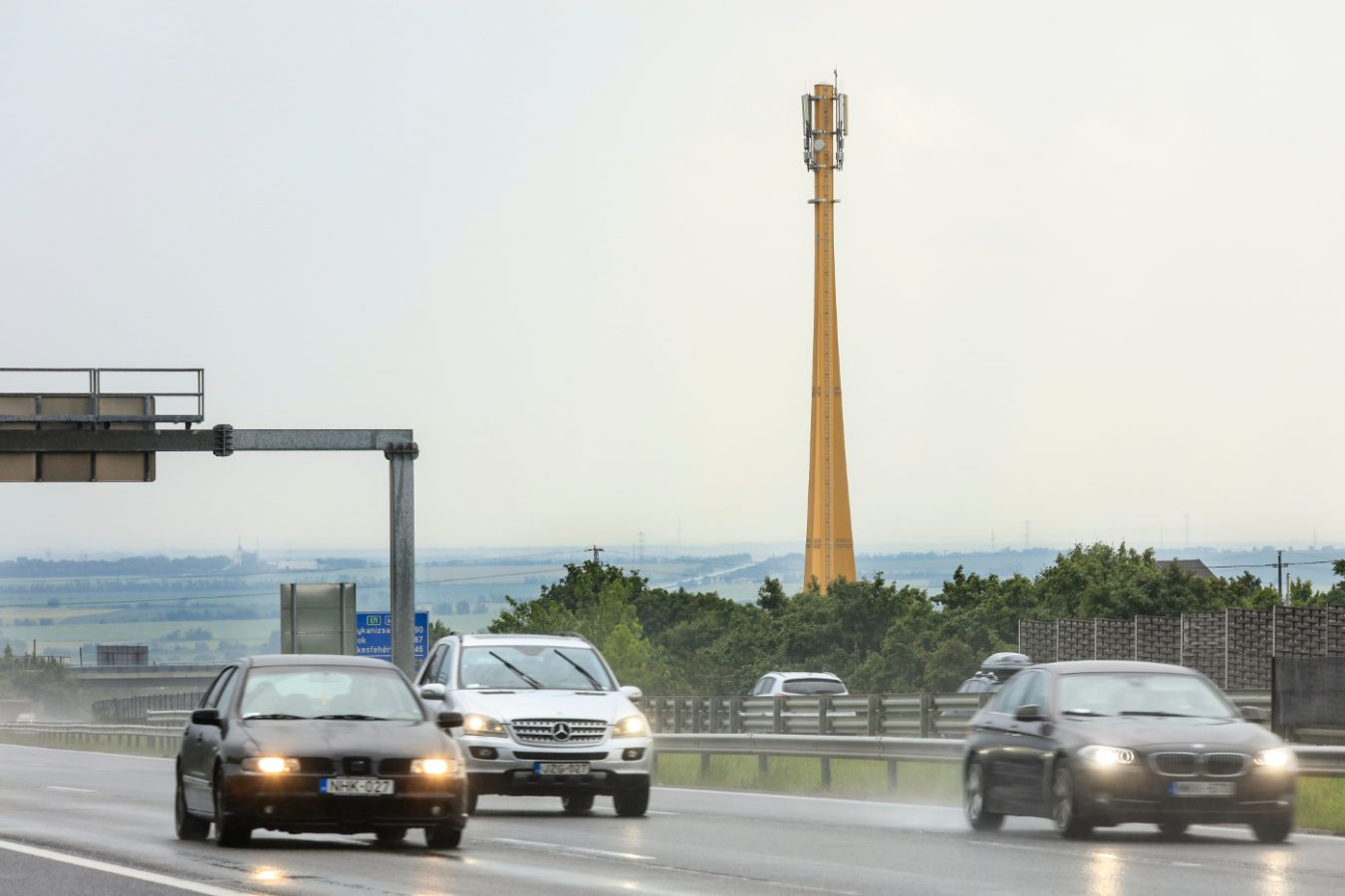 Traffic and in the background wooden telecommunication mast.
