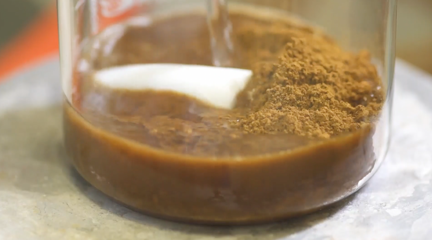 Brown lignin powder and water in a transparent glass.