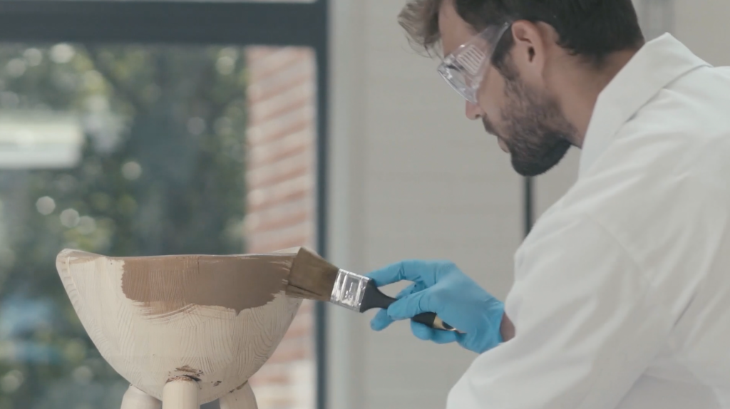 Man in a white laboratory coat is spreading lignin coating to a wood product.